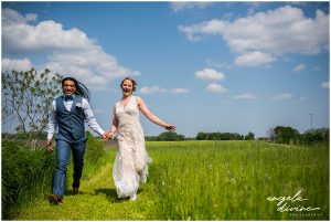bride and groom running through field
