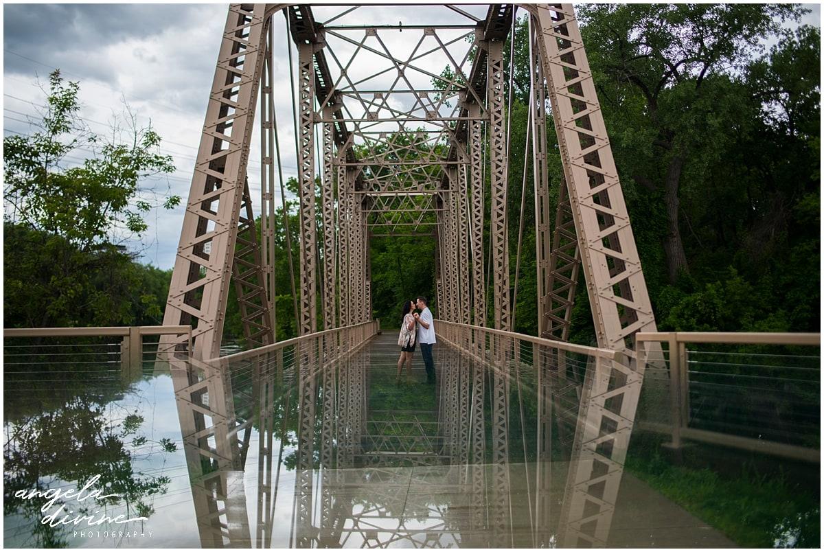 Boom Island Park Engagement posing on bridge