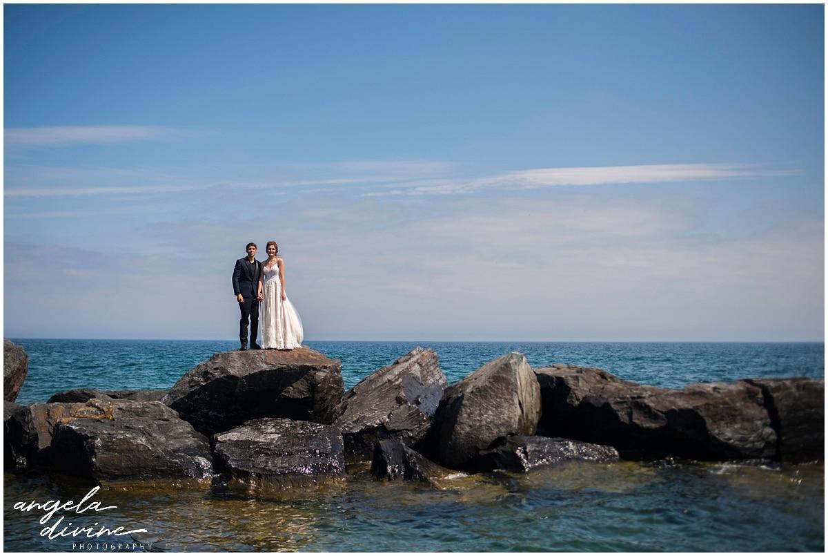 bride and groom posing on rocks in lake