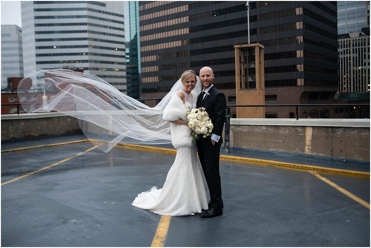 Woman's Club Minneapolis Wedding bride and groom in parking lot as veil blows in wind
