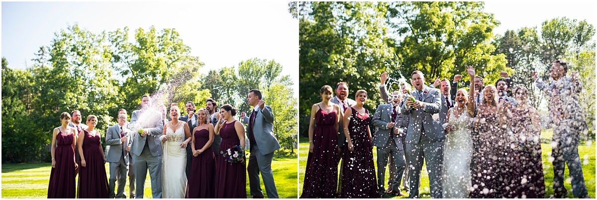 groom popping champagne with bridal party